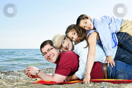 Happy family at beach stock photo, Portrait of a happy family having fun on a beach by Elena Elisseeva