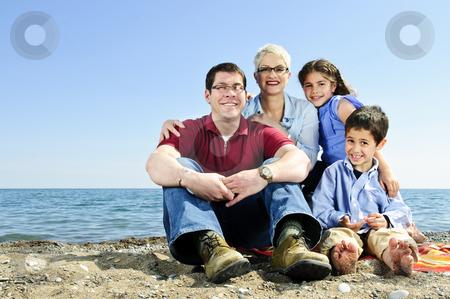 Happy family sitting at beach stock photo, Happy family sitting on towel at sandy beach by Elena Elisseeva
