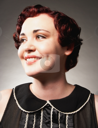 Woman Smiling stock photo, A young woman is smiling and looking up and away from the camera.  Vertically framed shot. by Media Deva
