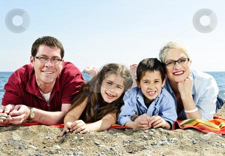 Happy family at beach stock photo, Happy family laying on towel at sandy beach by Elena Elisseeva