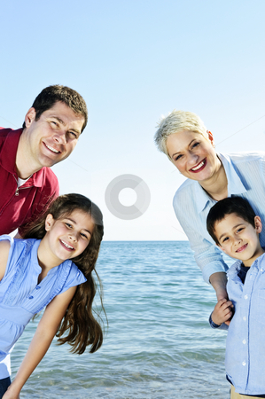 Happy family stock photo, Welcoming happy family of four at lake by Elena Elisseeva