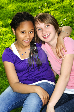 Girl friends stock photo, Two teenage girls sitting on grass and hugging by Elena Elisseeva