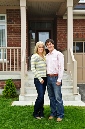 Happy couple at home stock photo, Young happy couple standing in front of house by Elena Elisseeva