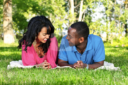 Happy couple in park stock photo, Young romantic couple enjoying summer day in park by Elena Elisseeva