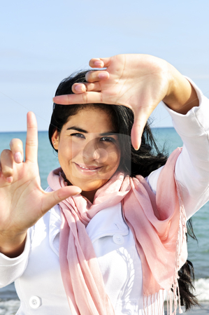 Beautiful young woman framing her face stock photo, Portrait of beautiful smiling brunette girl framing her face at beach by Elena Elisseeva