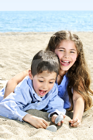 Brother and sister at beach stock photo, Portrait of brother and sister playing in sand at the beach by Elena Elisseeva