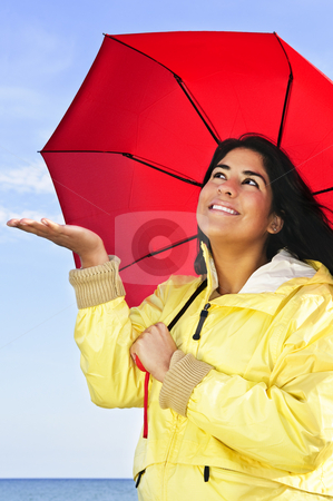 Beautiful young woman in raincoat with umbrella checking for rain stock photo, Portrait of beautiful smiling girl wearing yellow raincoat holding red umbrella checking for rain by Elena Elisseeva