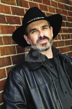 Bearded man in cowboy hat stock photo, Man with beard in cowboy hat and leather jacket by Elena Elisseeva