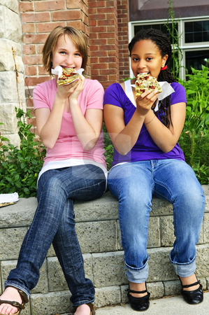 Girls eating pizza stock photo, Two teenage girls sitting and eating pizza by Elena Elisseeva