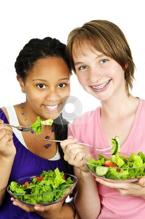 Girls having salad stock photo, Isolated portrait of two teenage girls eating salad by Elena Elisseeva
