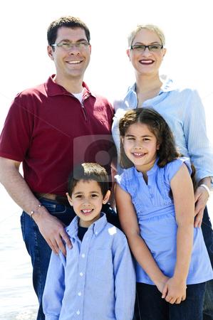 Happy family stock photo, Portrait of happy family of four standing by Elena Elisseeva