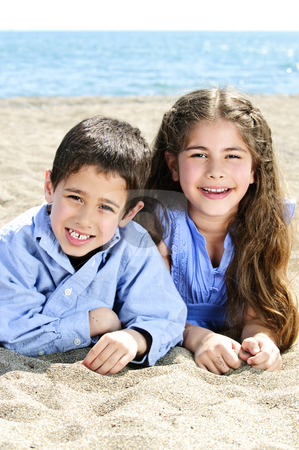 Brother and sister at beach stock photo, Portrait of brother and sister laying on sand at the beach by Elena Elisseeva
