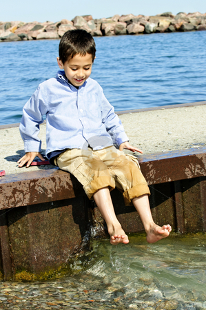 Boy playing on pier stock photo, Portrait of young boy dipping feet in lake from pier by Elena Elisseeva