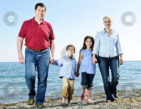Happy family stock photo, Portrait of happy family of four walking at beach by Elena Elisseeva