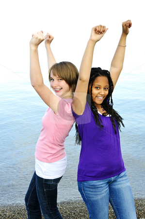 Happy girlfriends stock photo, Portrait of two teenage girl friends raising arms by Elena Elisseeva