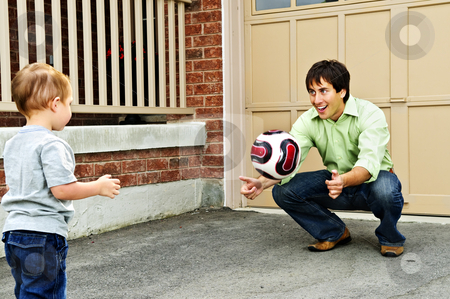 Father and son playing soccer stock photo, Father teaching son to play soccer on driveway by Elena Elisseeva