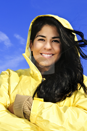 Beautiful young woman in raincoat stock photo, Portrait of beautiful smiling brunette girl wearing yellow raincoat against blue sky by Elena Elisseeva