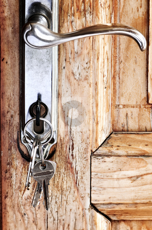 Door handle with keys stock photo, Set of keys in lock of old wooden door by Elena Elisseeva