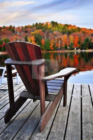 Wooden dock on autumn lake stock photo, Wooden dock with chair on calm fall lake by Elena Elisseeva