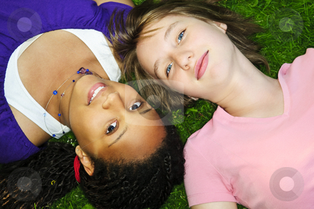 Girl friends stock photo, Two teenage girls laying on grass looking up by Elena Elisseeva