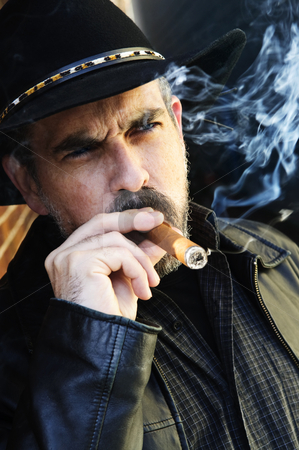 Bearded man smoking cigar stock photo, Man with beard in cowboy hat smoking cigar by Elena Elisseeva