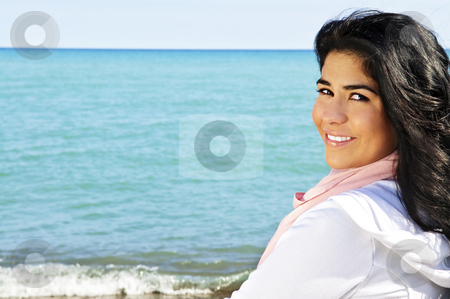 Beautiful young woman at beach stock photo, Portrait of beautiful smiling brunette girl at beach looking over her shoulder by Elena Elisseeva