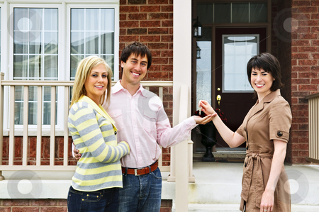 Happy couple with real estate agent stock photo, Happy couple getting keys to new house from real estate agent by Elena Elisseeva