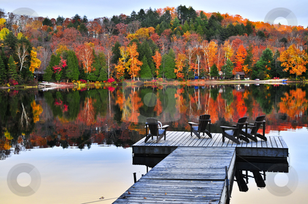 Wooden dock on autumn lake stock photo, Wooden dock with chairs on calm fall lake by Elena Elisseeva