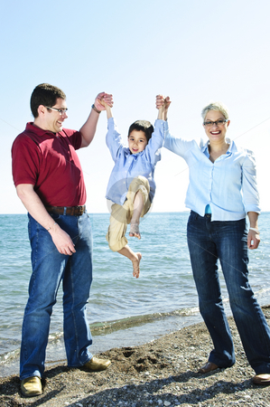 Happy family stock photo, Portrait of parents lifting boy playfully at beach by Elena Elisseeva