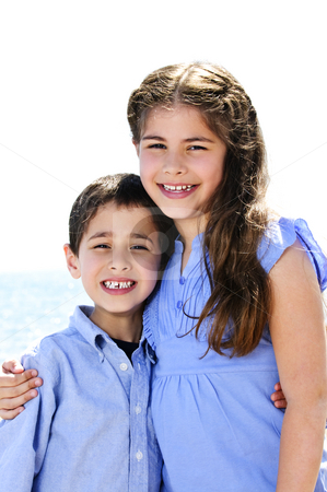 Brother and sister hugging stock photo, Portrait of siblings standing and hugging near lake by Elena Elisseeva
