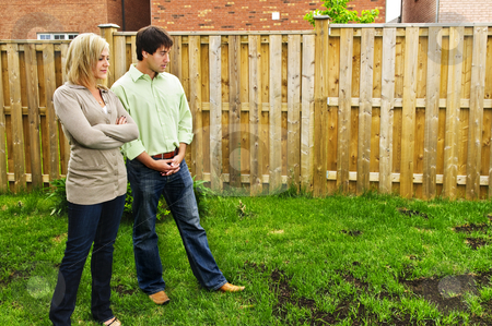 Couple concerned about lawn stock photo, Young couple worried about growing lawn in backyard of new home by Elena Elisseeva