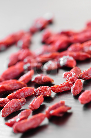 Goji berries stock photo, Scattered red dried goji berries on a table by Elena Elisseeva