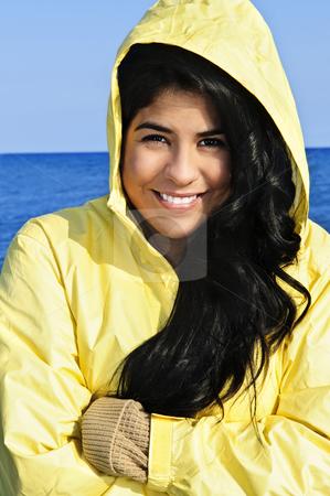 Beautiful young woman in raincoat stock photo, Portrait of beautiful smiling brunette girl wearing yellow raincoat by Elena Elisseeva