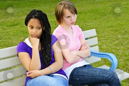 Bored teenage girls stock photo, Two bored teenage girls sitting on bench by Elena Elisseeva