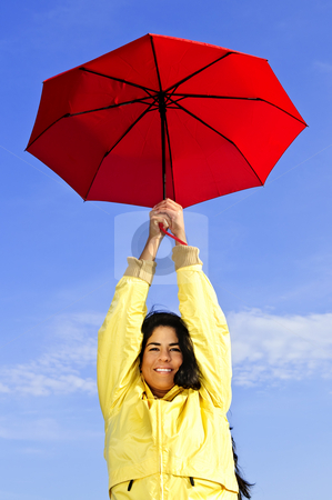 Beautiful young woman in raincoat with umbrella stock photo, Portrait of beautiful girl wearing yellow raincoat holding red umbrella on windy day by Elena Elisseeva