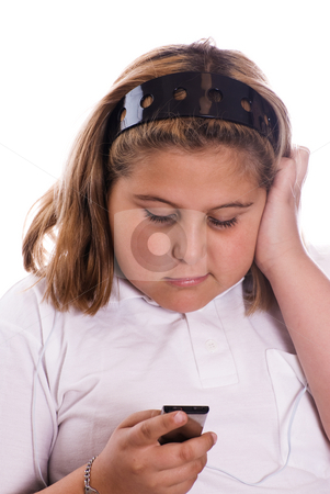 Girl Listening To Music stock photo, A young girl listening to her MP3 player isolated against a white background by Richard Nelson