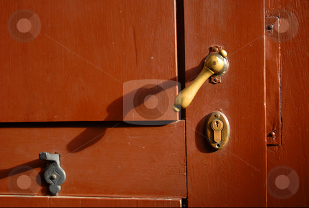 Bronce latch of a red door  stock photo, Bronce latch of a red wooden door by Cienpies Design
