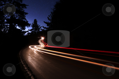 Car Light Trails in the Mountains on a Starry Night stock photo, Car Light Trails in the Mountains on a Starry Night Alongside the Highway. Noise is Present in the Sky Due to Shooting Conditions. by Katrina Brown