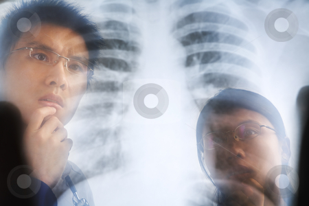 Asian doctor examining xray negative stock photo, Asian doctor examining xray negative / roentgen print. PS:the image taken from behind the xray print, so it may leave some soft noise on the people image behind it. by Rudyanto Wijaya