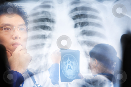 Asian doctors busy working stock photo, Asian doctors busy working in hospital. PS:the image taken from behind the xray print, so it may leave some soft noise on the people image behind it. by Rudyanto Wijaya