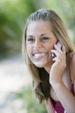 Smiling Woman Outdoors with Cell Phone  stock photo, Close-up of a smiling young woman using a cell phone in an outdoor setting. Vertical format. by Edward Bock
