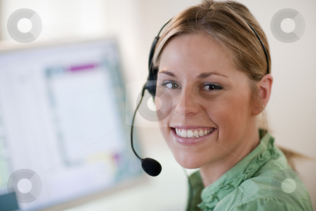 Young Woman Wearing Headset stock photo, Close-up of a young woman in front of a computer, wearing a headset and smiling at the camera. Horizontal format. by Edward Bock