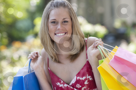 Happy Young Woman With Shopping Bags stock photo, Young woman holding shopping bags and smiling at the camera. Horizontal format. by Edward Bock