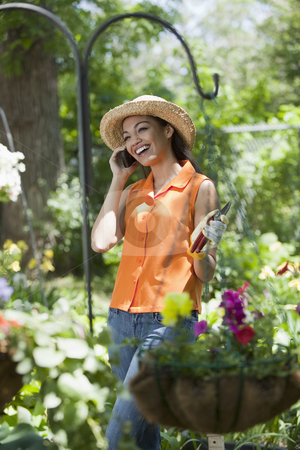 Young Woman With Cell Phone in Garden stock photo, A smiling young woman chats on a cellphone while taking a break from gardening. Vertical format. by Edward Bock