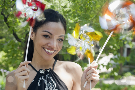 Young Woman Holding Pinwheels stock photo, Close-up of a happy young woman outdoors, holding three pinwheels.  Horizontal format. by Edward Bock