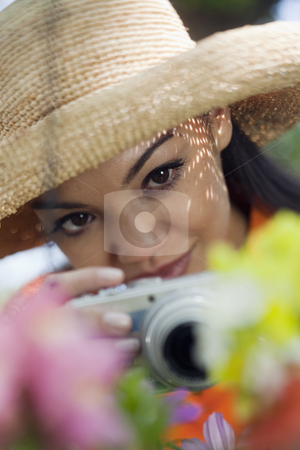 Young Woman Taking Pictures of Flowers stock photo, Close-up of a young woman in a sun hat, taking pictures of flowers. Vertical format. by Edward Bock