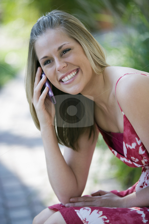 Smiling Woman Outdoors with Cell Phone stock photo, Smiling young woman talking on a cell phone in an outdoor setting. Vertical format. by Edward Bock