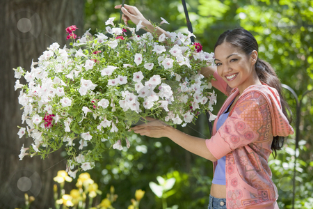 Young Woman in Garden stock photo, A young woman smiles while posing next to a hanging basket of flowers. Horizontal format. by Edward Bock