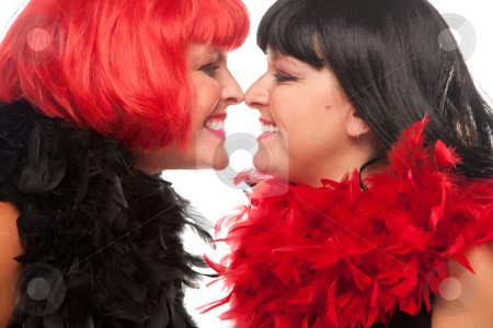 Red and Black Haired Women Smiling at Each Other stock photo, Red and Black Haired Women with Feather Boas Touching Noses and Smiling at Each Other. by Andy Dean