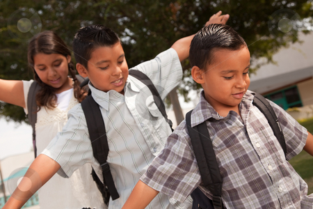 Cute Brothers and Sister Having Fun Walking to School stock photo, Cute Brothers and Sister with Backpacks Having Fun Walking to School. by Andy Dean